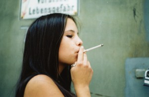 Jong meisje met sigaret in de mond.