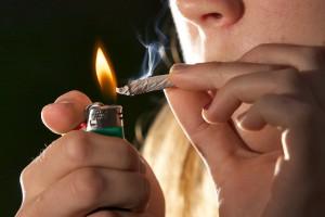 Meisje steekt een sigaret aan met een aansteker.